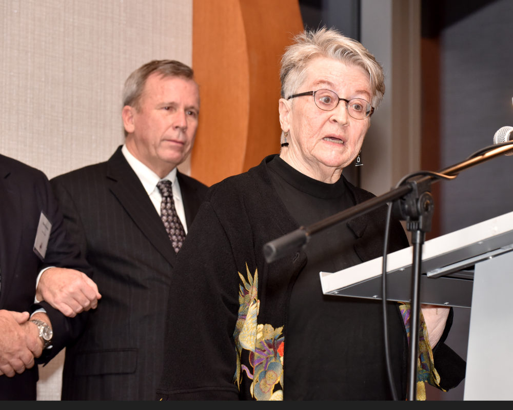 Pamela Heinrich MacPherson, talks about Inductee Frank Heinrich at the Induction into the Hall of Fame ceremony. Behind her are Heinrich family members.
